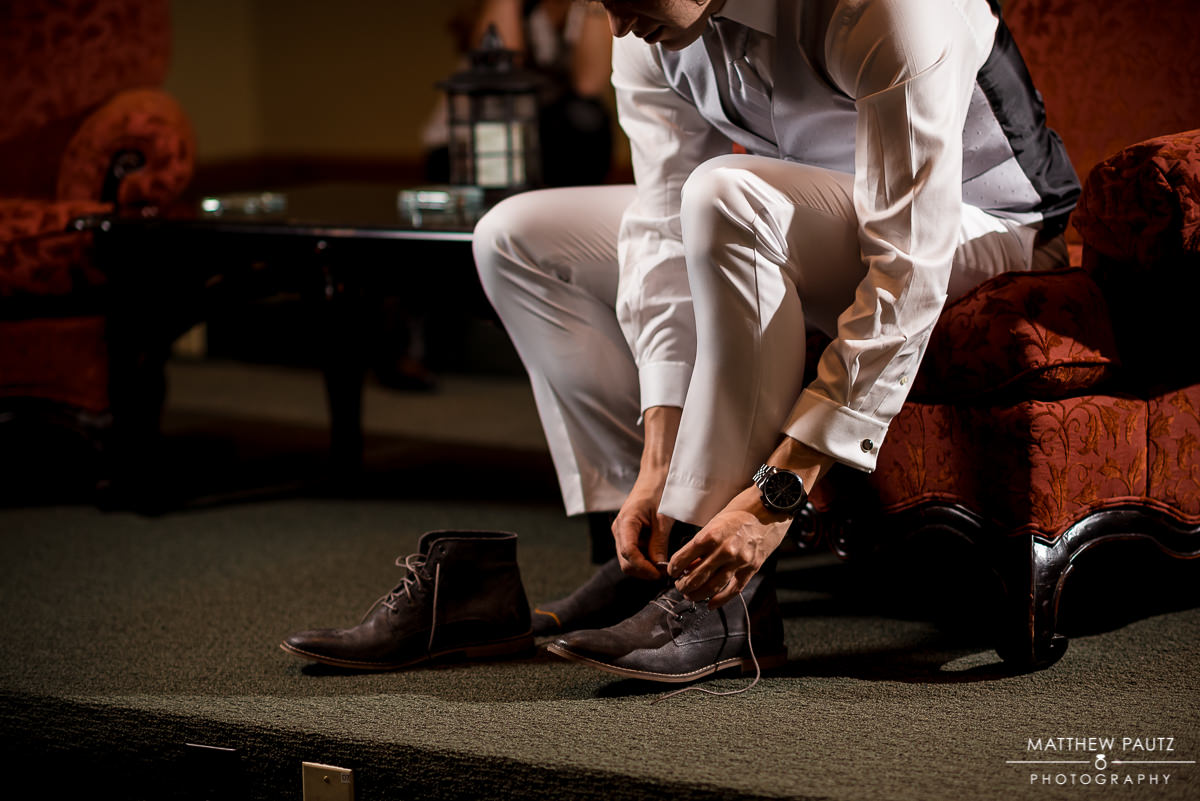 Crest center wedding photos | Groom putting shoes on