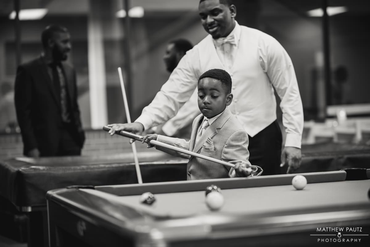 Groom helping young groomsman play pool before wedding
