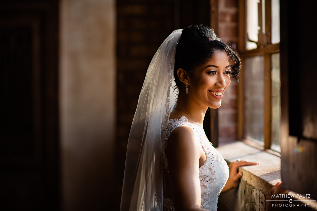 Bride in dress and veil looking out window