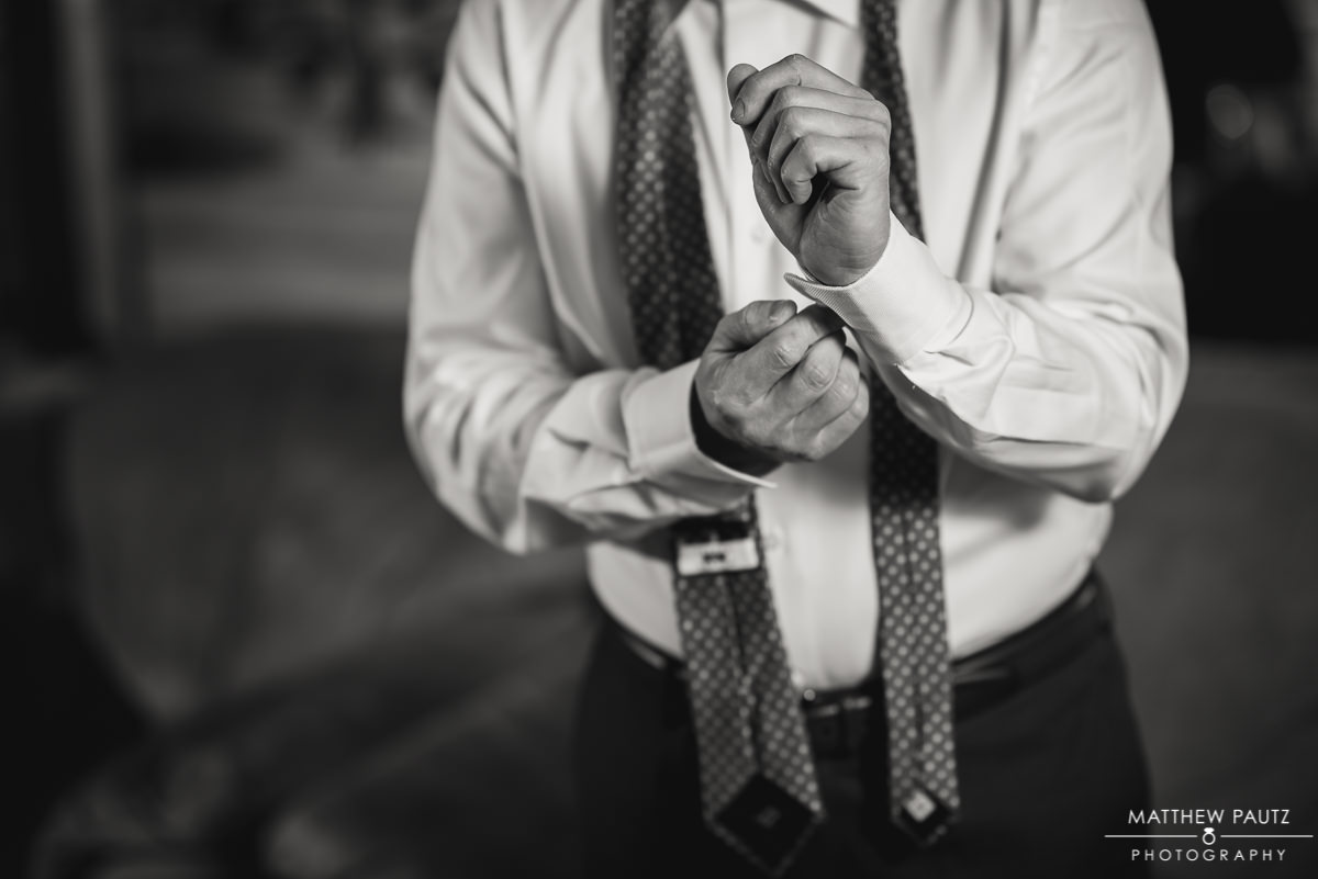 Closeup of groom adjusting cufflinks before wedding