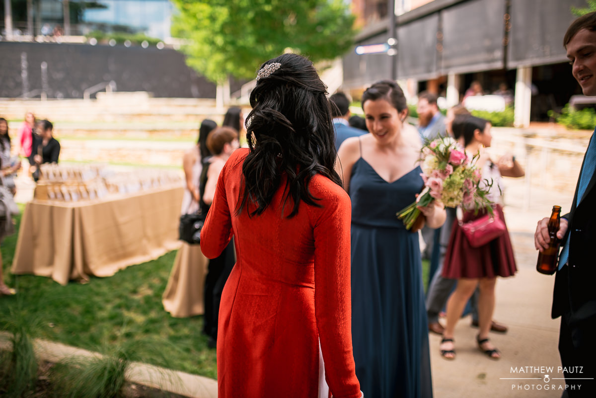 Bridesmaid checking out bride in dress